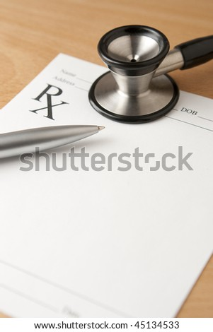 Prescription Document with Pen and Stethoscope. Critical focus on tip of pen.