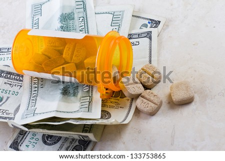 prescription jar spilled on the counter with american bills - stock photo