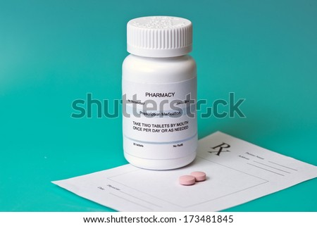 Prescription medication bottle and pills on aqua background with pad.  Label is not real. - stock photo