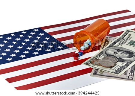 Prescription Medications laying on an American Flag with US Currency and Coins isolated on white - stock photo
