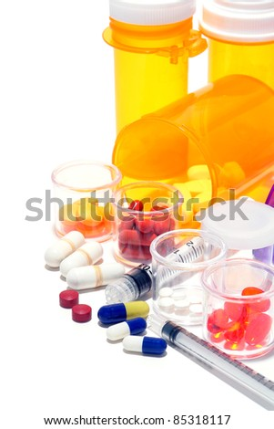 Prescription medicine pills and sample medication drug tablets in high dosage with syringes and pharmaceutical amber bottles for an aggressive medical treatment regimen to treat and cure a disease - stock photo