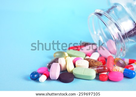 Prescription Pills and Medicine Medication Drugs spilling out of a bottle  - stock photo