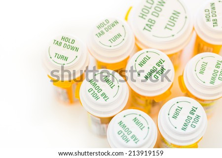 Prescription pills in yellow bottles on a white background. - stock photo