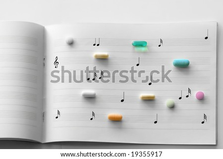 Prescription pills on white lined music note paper - stock photo