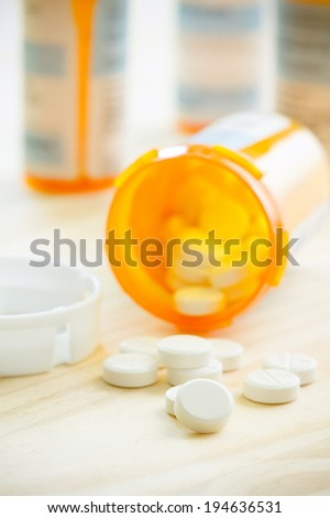 Prescription Pills - This is a high key shot of prescription pills spilling out from their bottle onto a wooden table top. Shot with a shallow depth of field. (Focus Set On Pills) - stock photo