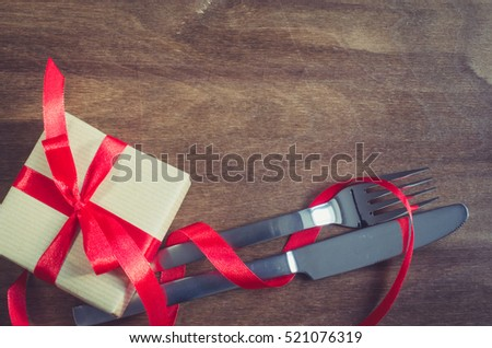 Present and Cutlery Decorated with Red Ribbon on Wooden Background. Selective Focus. Space for Text. Toned image.