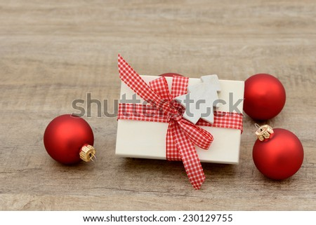 Present and xmas balls lying on wood - stock photo