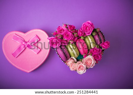 present box heart shape with flowers and macaroons violet background for valentines mother day easter with love - stock photo