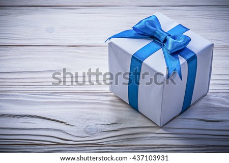 Present box with blue bow on wooden board celebrations concept. - stock photo