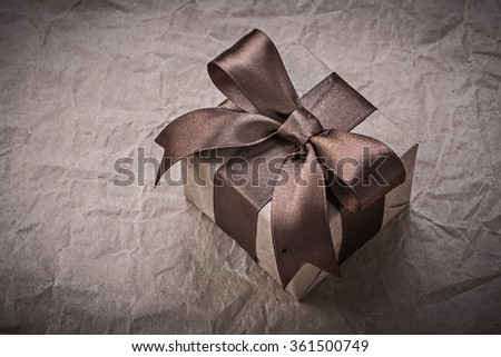 Present box with brown bow on wrapping paper holidays concept.