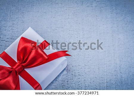 Present box with red bow on metallic background holidays concept. - stock photo