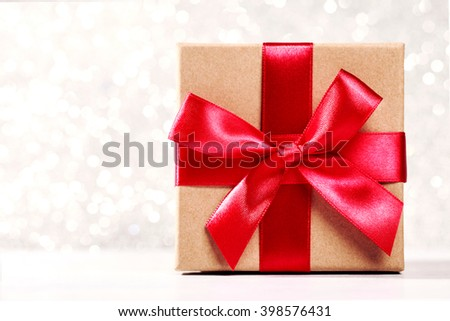 Present box with red bow on silver sparkling background - stock photo