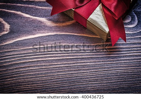 Present box with red satin ribbon on wooden board. - stock photo
