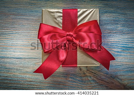 Present box with red tape on vintage wooden board holidays concept. - stock photo