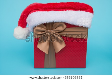 present box with santa claus hat on top on blue - stock photo
