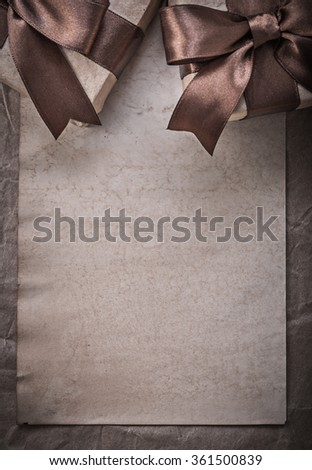 Present boxes tied bow sheet of wrapping paper celebration concept. - stock photo