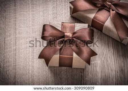 Present boxes with brown bows on wooden board celebration concept.