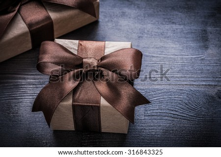 Present boxes with brown tied ribbons on vintage wooden surface.