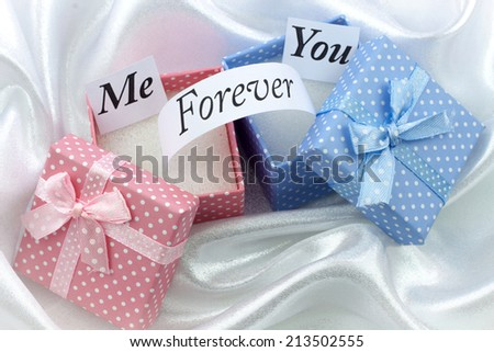 Present boxes with message on white satin. For female and male - stock photo