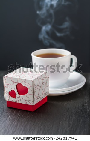 Present, chocolate candies box with hearts, cup od tea steaming on dark stone background - stock photo