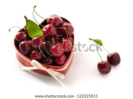 Present for Valentine's day. Red heart shaped box with sweet cherries and white ribbon. Isolated on white background. - stock photo