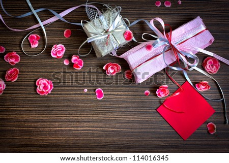 present,gift bow with petal from flowers   on wooden table/valentin day background