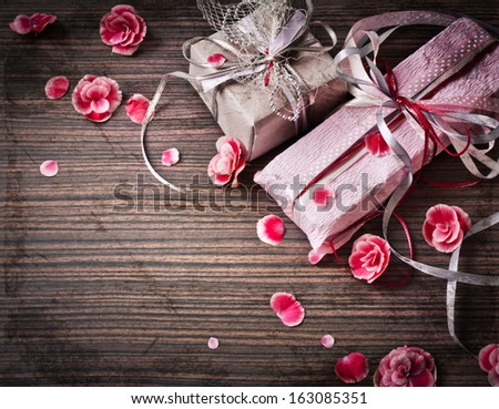 Present,gift bow with petal from flowers on wooden table/valentines day background