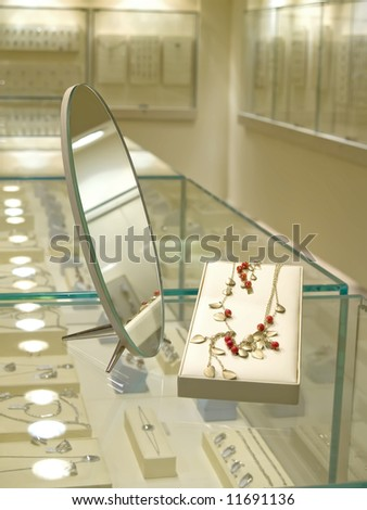 Present gift in jewerly shop. Necklace with red gems near mirror - stock photo