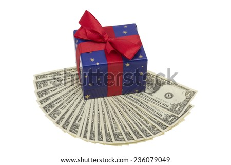 Present in blue wrapping paper with red ribbon on a fan of Dollar Notes isolated on white background