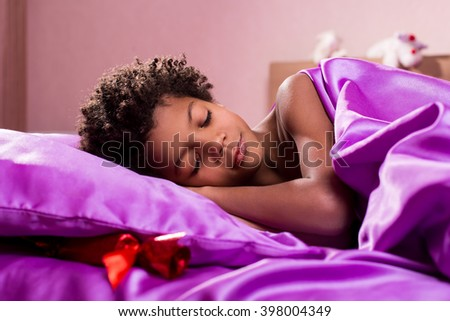 Present under boy's pillow. Afro child sleeping near present. Surprise is waiting for him. Wait until he wakes up. - stock photo