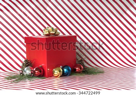 Present with bow on red and white striped Christmas background with copy space