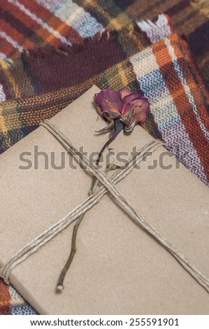Present wrapped, decorated with a flower, on a wool blanket