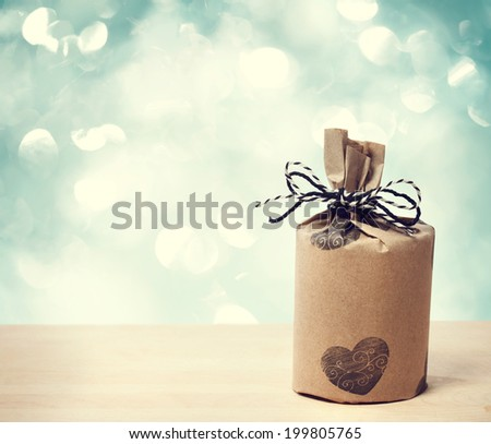 Present wrapped in a rustic earthy style on shiny blue background - stock photo