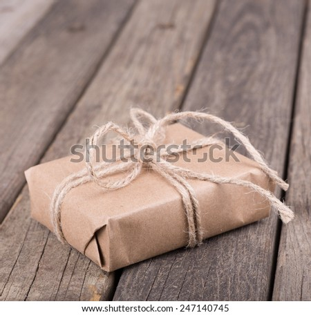 Present wrapped in brown paper and tied with string on a wood surface - stock photo