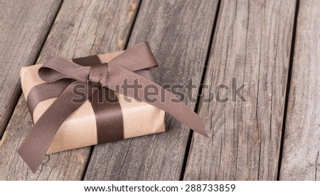 Present wrapped in brown paper on wood boards with copy space - stock photo