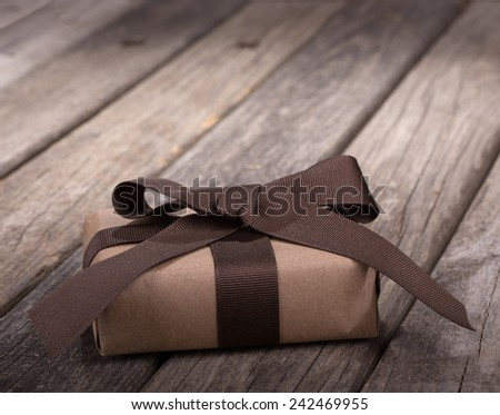 Present wrapped in ribbon and bow on old wood boards - stock photo