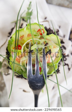 Presentation of a second tower gourmet dish of white rice and black with shrimp and zucchini - stock photo