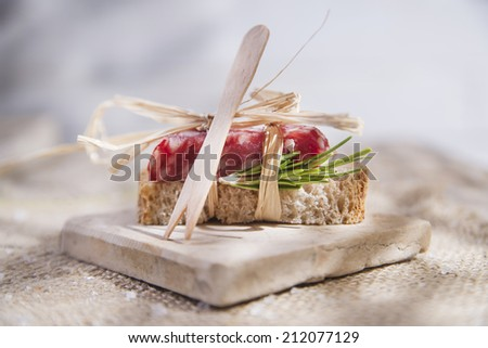 Presentation of a snack of bread and salami  - stock photo