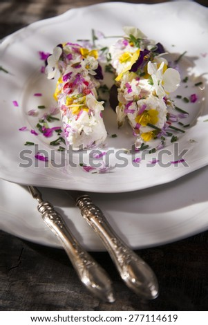 Presentation of goat cheese rolls with edible flowers - stock photo
