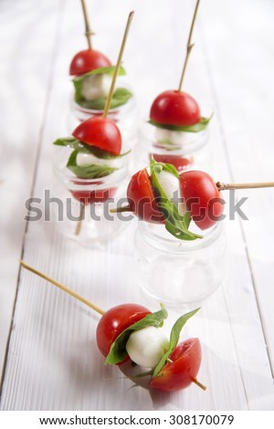 Presentation of small skewer caprese, tomato mozzarella and basil - stock photo