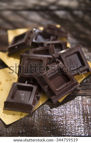 Presentation of some cubes of dark chocolate on wooden table