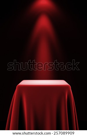 Presentation pedestal covered with a red silk cloth in front of a wall illuminated by a spot light - stock photo