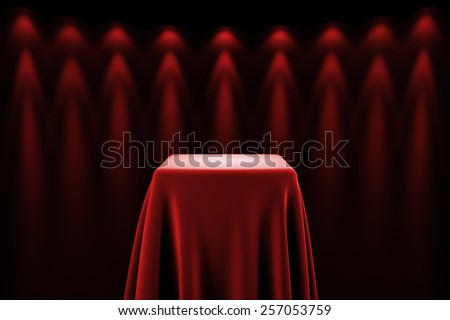 Presentation pedestal covered with a red silk cloth in front of a wall illuminated by spot lights - stock photo