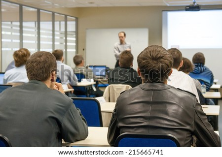 presenter near the screen and people sitting rear and watching the conference - stock photo