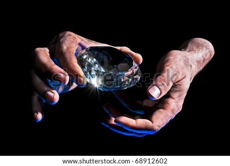 Presenting Diamond - Dirty male hand hold diamond against black background - blue lit from underside - stock photo