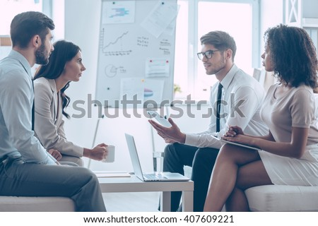 Presenting new business strategy. Young handsome man gesturing and discussing something with his coworkers while sitting on the couch at office - stock photo