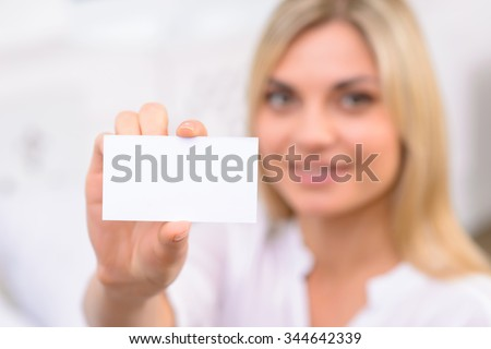 Presenting oneself. Appealing young woman reaching out to present her business card. - stock photo