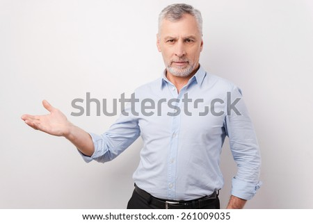 Presenting your product. Confident senior man in formalwear pointing away and looking at camera while standing against white background - stock photo
