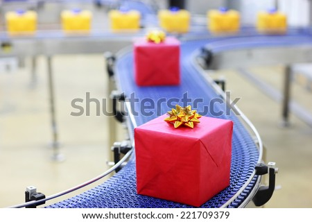 presents in boxes on conveyor belt in Christmas gifts factory  - stock photo