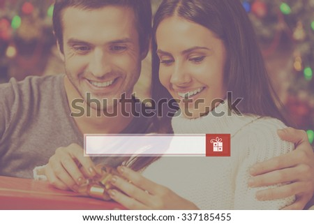Presents search. Happy young woman opening a gift box while her boyfriend sitting close to her and smiling with Christmas decoration in the background - stock photo